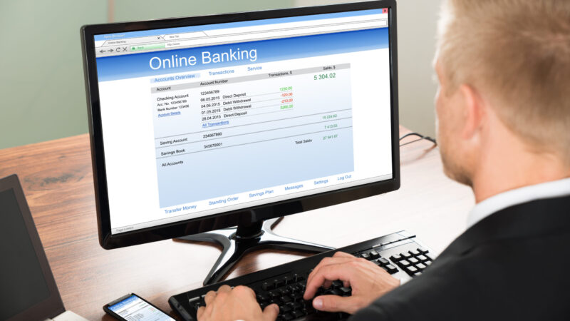 Close-up Of A Businessman Using Online Banking Service On Computer At Office