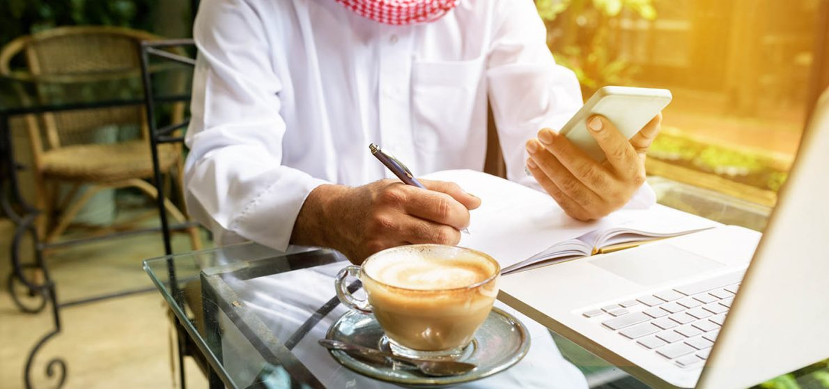Arab muslim business man ware white traditional clothing in hand writing something on paper and look at smart phone with laptop on coffee glass table