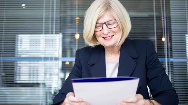 Positive senior HR worker holding personal file and reading them. Cheerful smart employee working with business papers at table. Documents concept