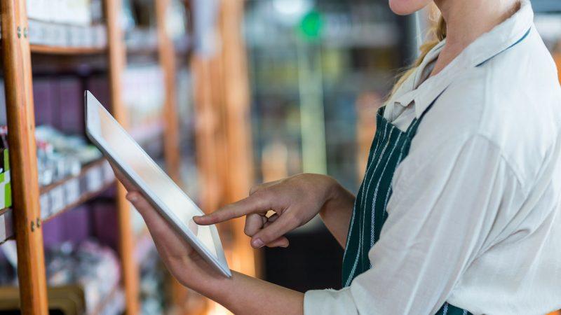Female staff using digital tablet in supermarket