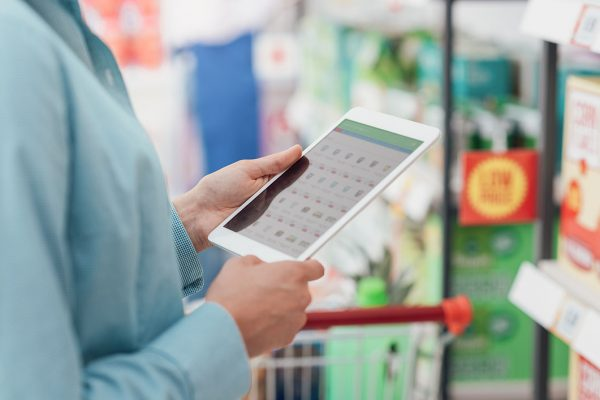Woman shopping at the supermarket, she is connecting with her digital tablet and searching offers online, hands close up